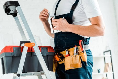 Photo for Cropped view of installer with tool belt holding construction stapler - Royalty Free Image