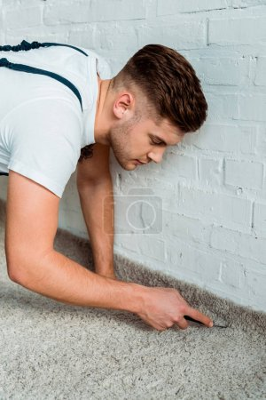 Photo for Handsome installer holding cutter near carpet and brick wall - Royalty Free Image