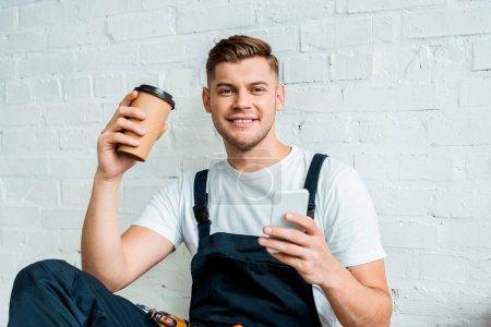 Photo pour Installateur gai en utilisant smartphone tout en tenant tasse en papier - image libre de droit