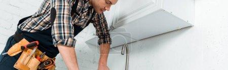 Foto de Foto panorámica del instalador de pie cerca de grifo en la cocina. - Imagen libre de derechos