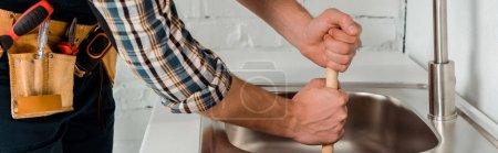 Foto de Tiro panorámico de fontanero que se hunde cerca del lavabo en la cocina. - Imagen libre de derechos