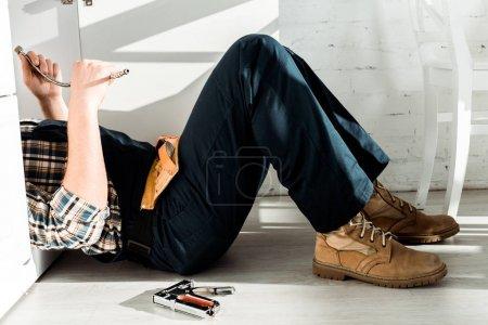 Foto de Vista panorámica del instalador que se encuentra en el piso cerca del armario de cocina. - Imagen libre de derechos