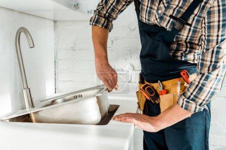 Ausgeschnittene Ansicht des Installateurs mit metallischem Waschbecken in der Nähe des Wasserhahns in der Küche
