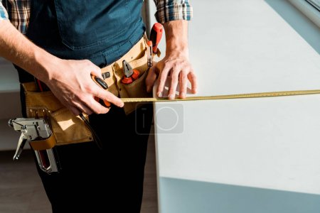 Photo for Cropped view of installer measuring windowsill while holding measuring tape - Royalty Free Image