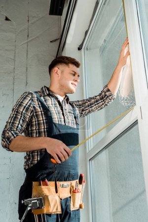 Photo for Installer standing near windows and holding measuring tape - Royalty Free Image