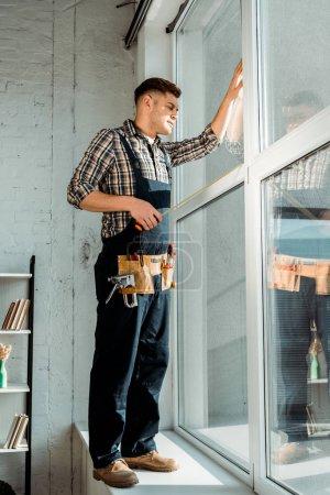 Foto de Instalador que se encuentra en windowsill cerca de ventanas y sostiene la medición de cinta. - Imagen libre de derechos