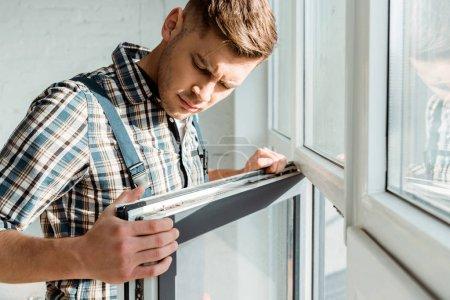 Photo pour Selective focus (focalisation sélective) de l'installateur touchant la fenêtre - image libre de droit