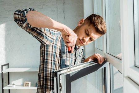Foto de Enfoque selectivo del controlador de tornillo de sujeción concentrado del instalador cerca de ventana. - Imagen libre de derechos