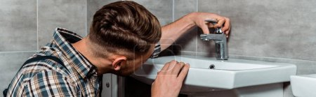panoramic shot of installer touching faucet in bathroom