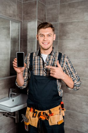 happy installer pointing with finger at smartphone with blank screen in bathroom