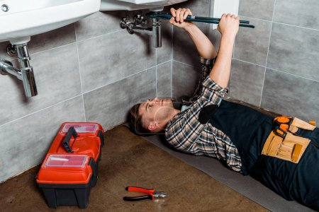 Foto de Handsome installer holding slip joint pliers near pipe and tool box. - Imagen libre de derechos