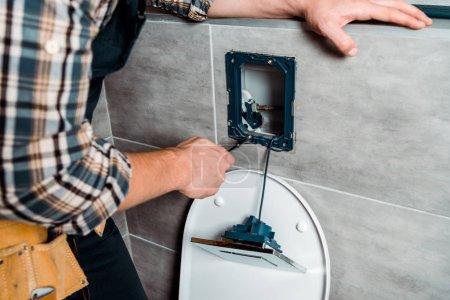 Foto de Vista borrosa del controlador de tornillo de soporte del instalador cerca de WC. - Imagen libre de derechos
