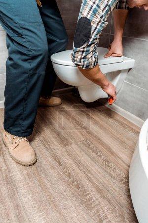 Photo pour Vue recadrée de l'homme installant des toilettes blanches - image libre de droit