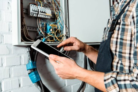Photo for Cropped view of electrician using digital tablet with blank screen near switchboard - Royalty Free Image