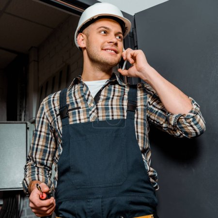 cheerful installer in safety helmet holding screwdriver while talking on smartphone