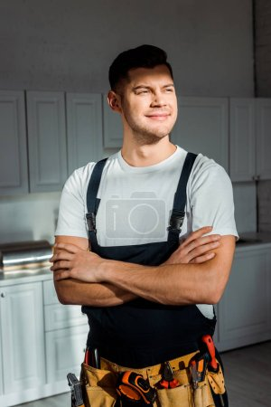 Photo for Sunshine on cheerful installer in overalls standing with crossed arms - Royalty Free Image