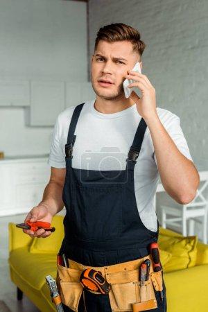 Foto de Instalador guapo en overalls con cortadora y hablando en smartphone. - Imagen libre de derechos