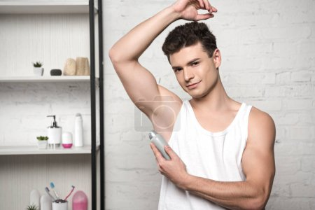 young man in white sleeveless shirt looking at camera while spraying deodorant on underarm