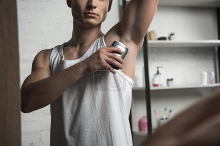 cropped view of man in white sleeveless shirt applying deodorant on underarm