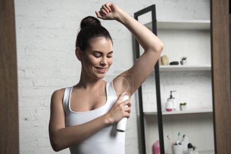 Photo pour Femme heureuse appliquant déodorant sur les aisselles tout en se tenant près du miroir à la maison - image libre de droit