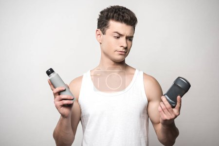 Photo for Skeptical man in white sleeveless shirt holding deodorants isolated on grey - Royalty Free Image