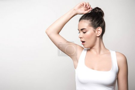 shocked woman in white sleeveless shirt looking at underarm isolated on grey