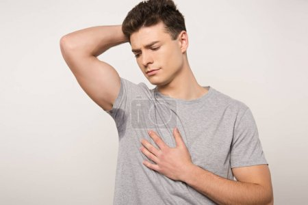 Photo for Displeased man in grey t-shirt with sweaty underarm holding hand of chest isolated on grey - Royalty Free Image