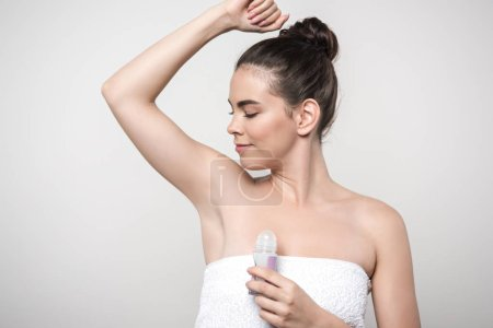 happy woman looking at underarm while holding deodorant isolated on grey