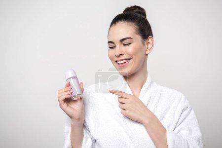 glückliche Frau im Bademantel zeigt mit dem Finger auf Deo isoliert auf grau