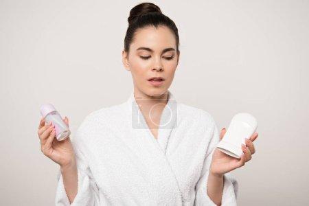 Photo pour Femme sceptique en peignoir tenant des déodorants isolés sur gris - image libre de droit