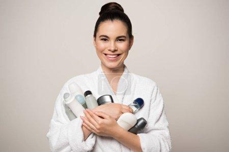 Photo pour Femme joyeuse en peignoir tenant différents déodorants tout en regardant la caméra isolée sur gris - image libre de droit