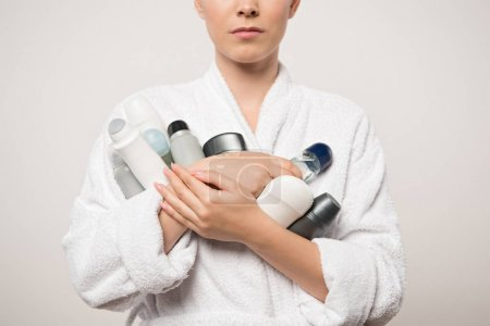 Photo for Partial view of woman in bathrobe holding different deodorants isolated on grey - Royalty Free Image