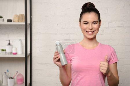 Photo pour Femme gaie souriant à la caméra et montrant pouce vers le haut tout en tenant déodorant - image libre de droit