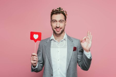 Photo pour Homme heureux dans la couronne montrant ok signe et carte de maintien avec coeur pour la Saint-Valentin, isolé sur rose - image libre de droit