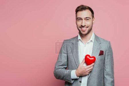 Photo pour Happy man tenant le cœur rouge pour la journée des valentins, isolé sur rose - image libre de droit
