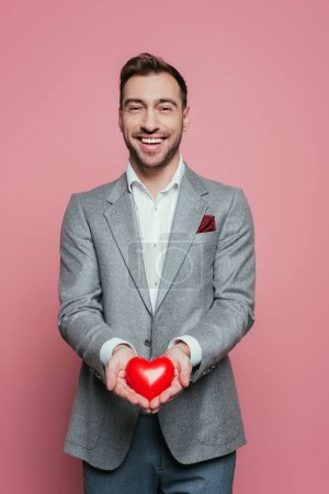 Photo pour Beau gai tenant le cœur rouge pour valentins jour, isolé sur rose - image libre de droit