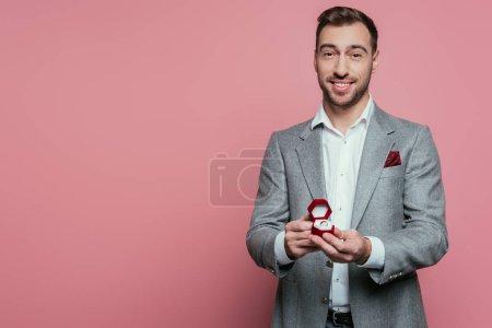 Photo pour Homme souriant tenant boîte avec bague de proposition, isolé sur rose - image libre de droit