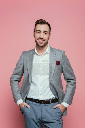 Photo for Bearded positive man in grey suit with hands in pockets, isolated on pink - Royalty Free Image