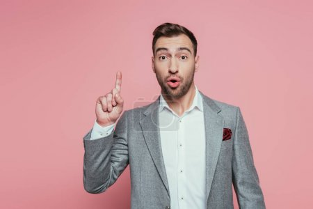 excited bearded man in grey suit pointing up, isolated on pink