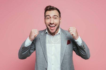 Photo pour Excité homme réussi geste en costume gris, isolé sur rose - image libre de droit