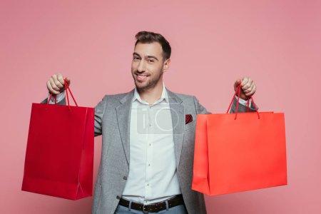Photo pour Homme heureux et positif tenant des sacs à provisions, isolé sur rose - image libre de droit