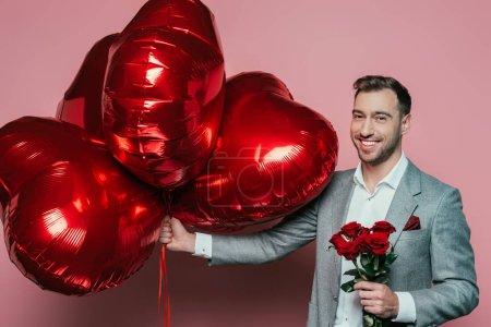 Photo pour Homme émotionnel tenant des roses et des ballons rouges pour les valentins jour en rose - image libre de droit