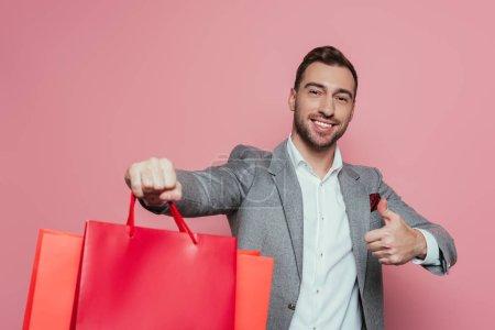 Photo pour Homme souriant tenant des sacs à provisions et montrant pouce levé, isolé sur rose - image libre de droit