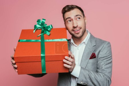 smiling man in suit holding big gift box, isolated on pink