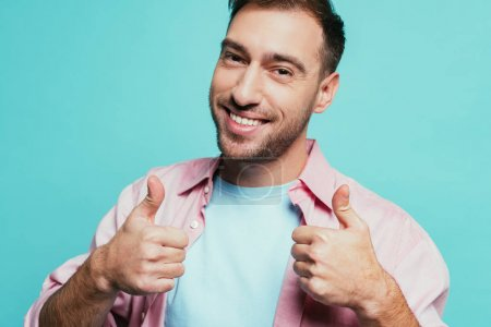 Photo for Cheerful handsome man showing thumbs up, isolated on blue - Royalty Free Image
