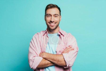 Photo pour Bel homme souriant aux bras croisés, isolé en bleu - image libre de droit