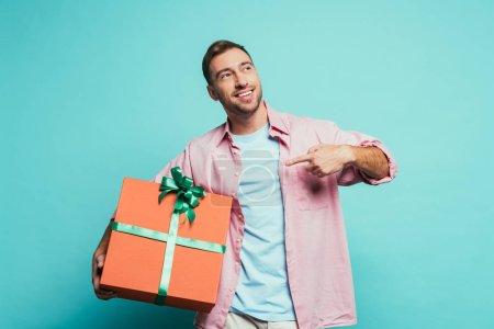 Photo pour Homme barbu heureux pointant vers une grande boîte-cadeau, isolé sur bleu - image libre de droit