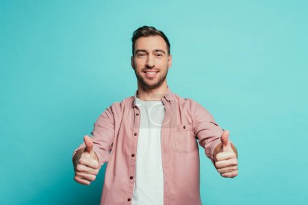 smiling handsome man showing thumbs up, isolated on blue
