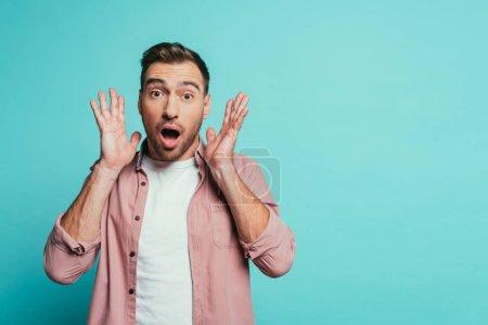 Photo pour Choqué beau homme criant isolé sur bleu - image libre de droit