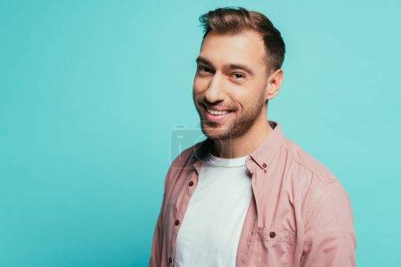 Photo pour Joyeux bel homme souriant et regardant la caméra, isolé sur bleu - image libre de droit